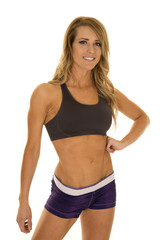 fit woman in purple shorts pose hand on stomach smile