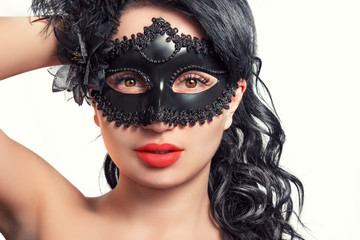 Portrait of a beautiful young woman in a black mask