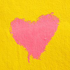 red heart on  yellow cement wall