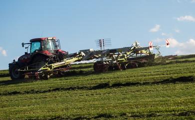Traktor auf Wiese beim Heuwenden