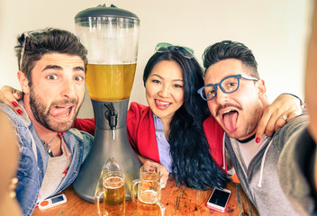Happy friends taking selfie with funny tongue out and beer tower