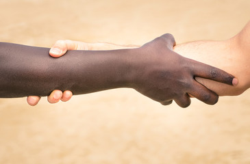 Black and white hands in modern handshake against racism
