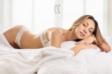 Sexy blonde woman lying on bed