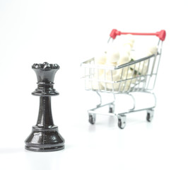 Black queen with blurred white pawn inside toy trolley
