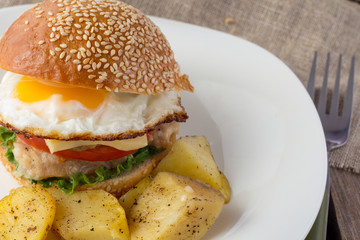 Cheeseburger with fried egg and potato wedges