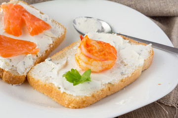 Wheat bread toasts with cream cheese, smoked salmon and shrimp
