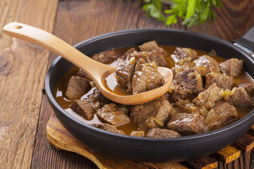 Beef stew - wooden background