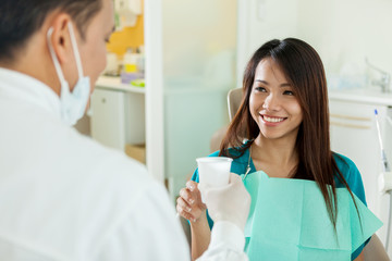 Smiling asian woman is taking a glass of water from her dentist