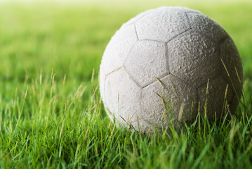 Football on green grass with soft light