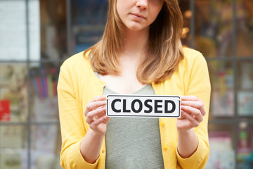 Close Up Of Shop Owner Holding Closed Sign