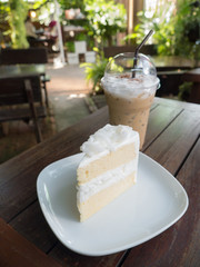 Coconut cake on white plate and cup of ice coffee