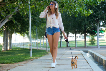 Beautiful young woman walking with her dog in the park.
