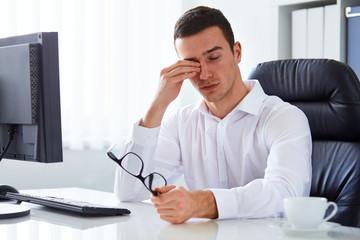Tired businessman rubbing his eye