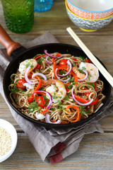 Chinese buckwheat noodles with spicy shrimp in a frying pan