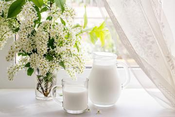 Bouquet of bird cherry and milk on the window