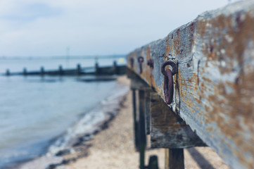 Wooden structure with rusty chain on beach