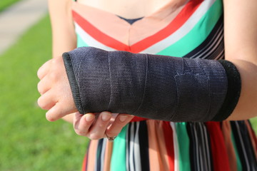 Girl in colorful dress holding her broken arm in cast
