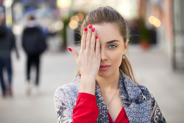 Young beautiful woman closes her eyes with his hand