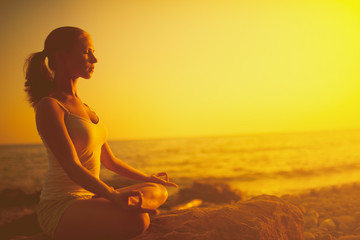 Wall Mural - woman meditating in lotus pose on the beach at sunset