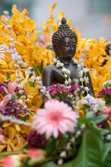 A Buddha statue covered with flower petals