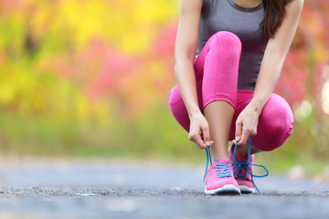 Running shoes - woman tying shoe laces closeup of