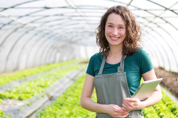 Portrait of an attractive farmer in a greenhouse using tablet