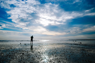 man silhouette standing at the beach