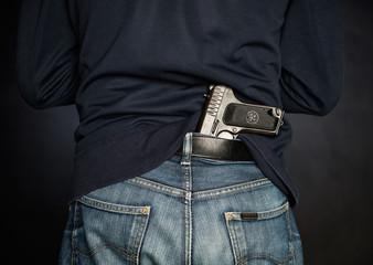 Hided handgun under the denim belt.