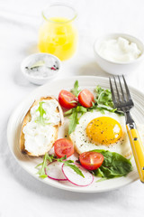 fried egg with tomatoes, arugula, radish, and toast with cheese