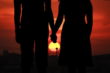 silhouette of mother hold one's hand her daughter at city