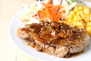 Beef Steak on white dish, plank wood background.