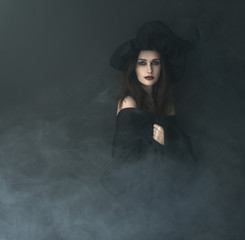 slender witch in a smoke on  black background