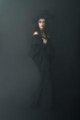 slender witch in a dark fog