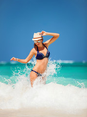 Happy fashion woman jumping on the waves of sea