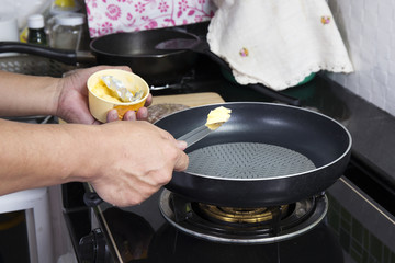 Chef putting butter to the pan
