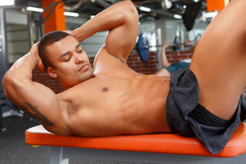Young pleasant man doing abdominal crunches in gym
