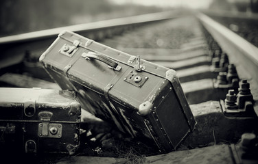 Not the color image of forgotten suitcases on rails.