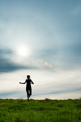Silhouette of a girl with braids running in a meadow