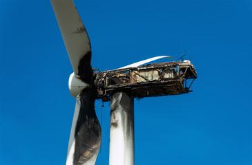 View of Burned wind turbine over blue sky.