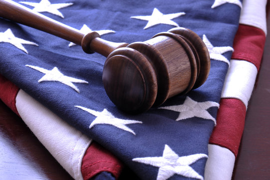 Wooden judge's gavel and American flag.
