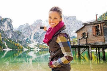 Smiling woman at Lake Bries aiming digital camera at Dolomites