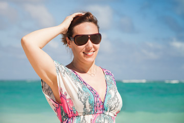 Young happy woman in sunglasses on a sea coast