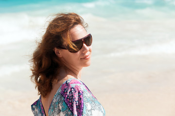 Young beautiful woman in sunglasses on a beach