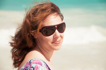 Young smiling woman in sunglasses on a beach