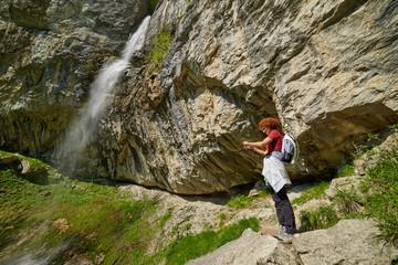 Woman taking photos near the waterfall