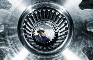Wall Mural - engineer, mechanic, seen through a giant cogwheels axle