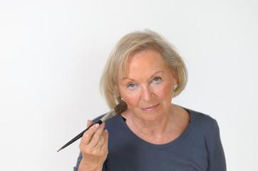 Attraktive Seniorin trägt sich Rouge mit einem Pinsel auf