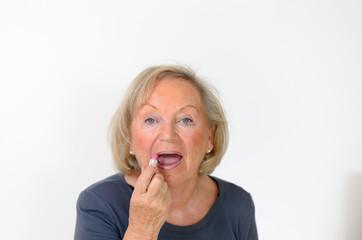 Attraktive ältere Rentnerin schminkt sich ihre Lippen