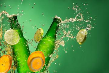 Bottles of fruit beer with splash, on gree