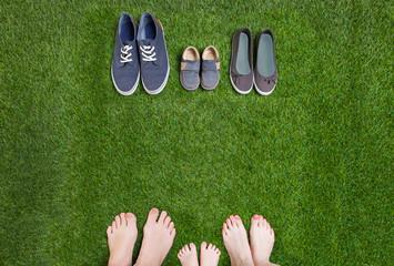 Family legs  standing  opposite shoes on  grass